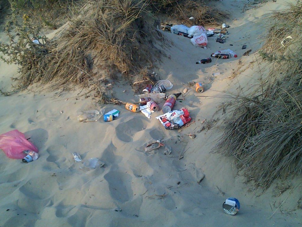 Playa ensuciada con lata y plásticos en el mar
