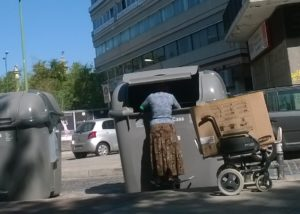 mujer pobre buscando en un contenedor